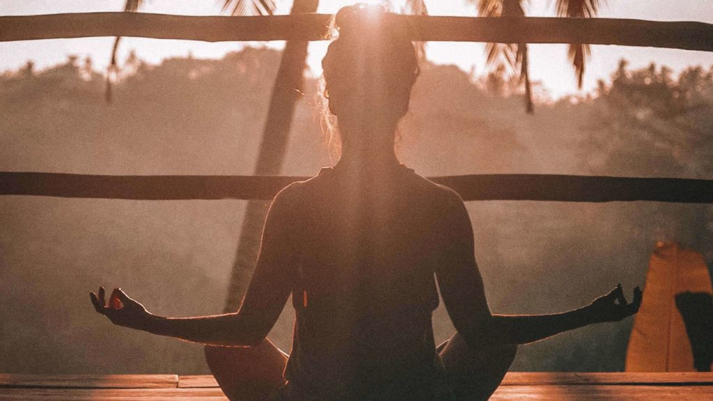 A woman meditating at sunrise image for a life purpose post by Linda Salvin Ph.D